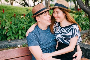 Asian couple sitting on the bench in public park with copy space with romance and happiness
