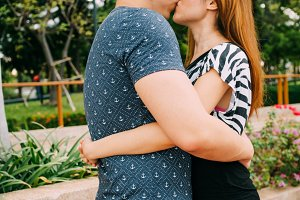 Romantic couple kissing in outdoor public park with love