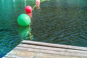 Multicolored buoys on dark little wavy water. warning Sign for swimmers