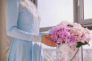 Wedding flowers in hands of young female bride in blue dress
