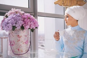 Beautiful bride in muslim wedding clothes with cup of coffee sitting by the window