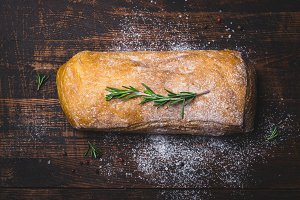 Italian ciabatta bread with branch of rosemary on dark wooden background