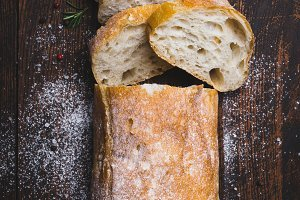 Italian ciabatta bread cut in slices on dark wooden background