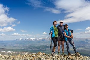 Hikers with backpacks enjoying valley view from top