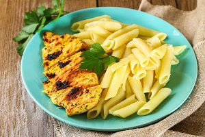Grilled chicken breast and Penne pasta with spices and Basil. A delicious dinner in the rustic style. Selective focus