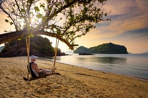 Young man enjoys sunset on a swing at a beach in Thailand