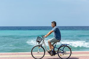 Man cycling by the sea