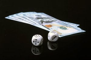 Risk of business. Wooden dices and money. Devil's bones on black mirror table.