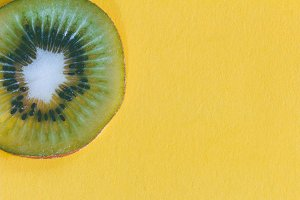 Sliced kiwi on yellow background