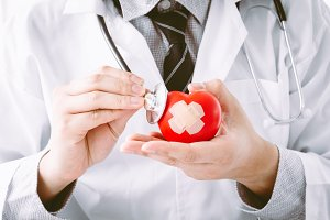 Male doctor holding red heart