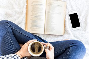 Woman with coffee reading a book