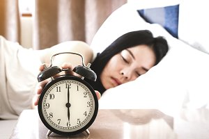 Woman sleeping and alarm clock