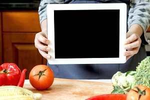 Woman holding tablet in kitchen