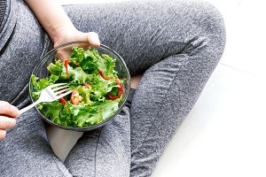 Fit healthy woman eating fresh salad