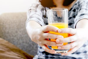 Woman holding glass with tasty juice