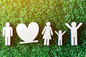 Wooden family on green grass