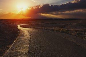 Road sunset between hills.