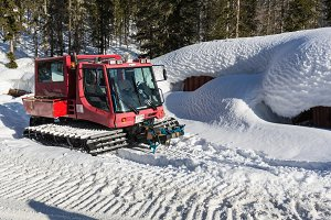 Red ratrak snowcat in winter mountains A red snow tucker covered with snow in Krkonose mountain. Red over-snow vehicle,