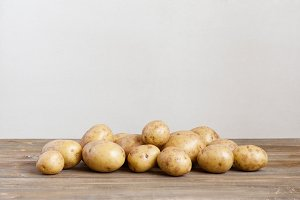 Fresh potatoes on the wooden table