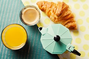 Breakfast setting with coffee, croissant and orange juice, top view
