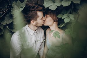 couple kissing in green leaves