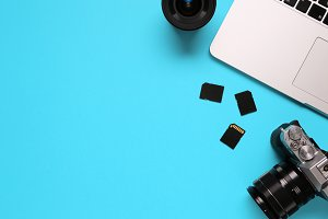 Top view of a desktop of a photographer consisting on a camera, a laptop, a notebook and a memory card on a blue desk background - copy space.