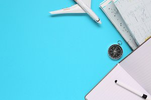 Travel , trip vacation, tourism mockup - compass, mobile phone, pen and toy airplane and touristic map on blue background. Copy space