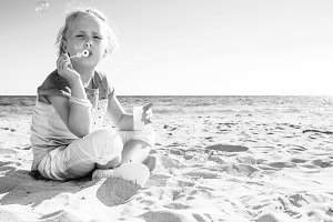 smiling modern child in colorful shirt on beach blowing bubbles