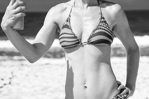 young woman on beach applying suntan lotion