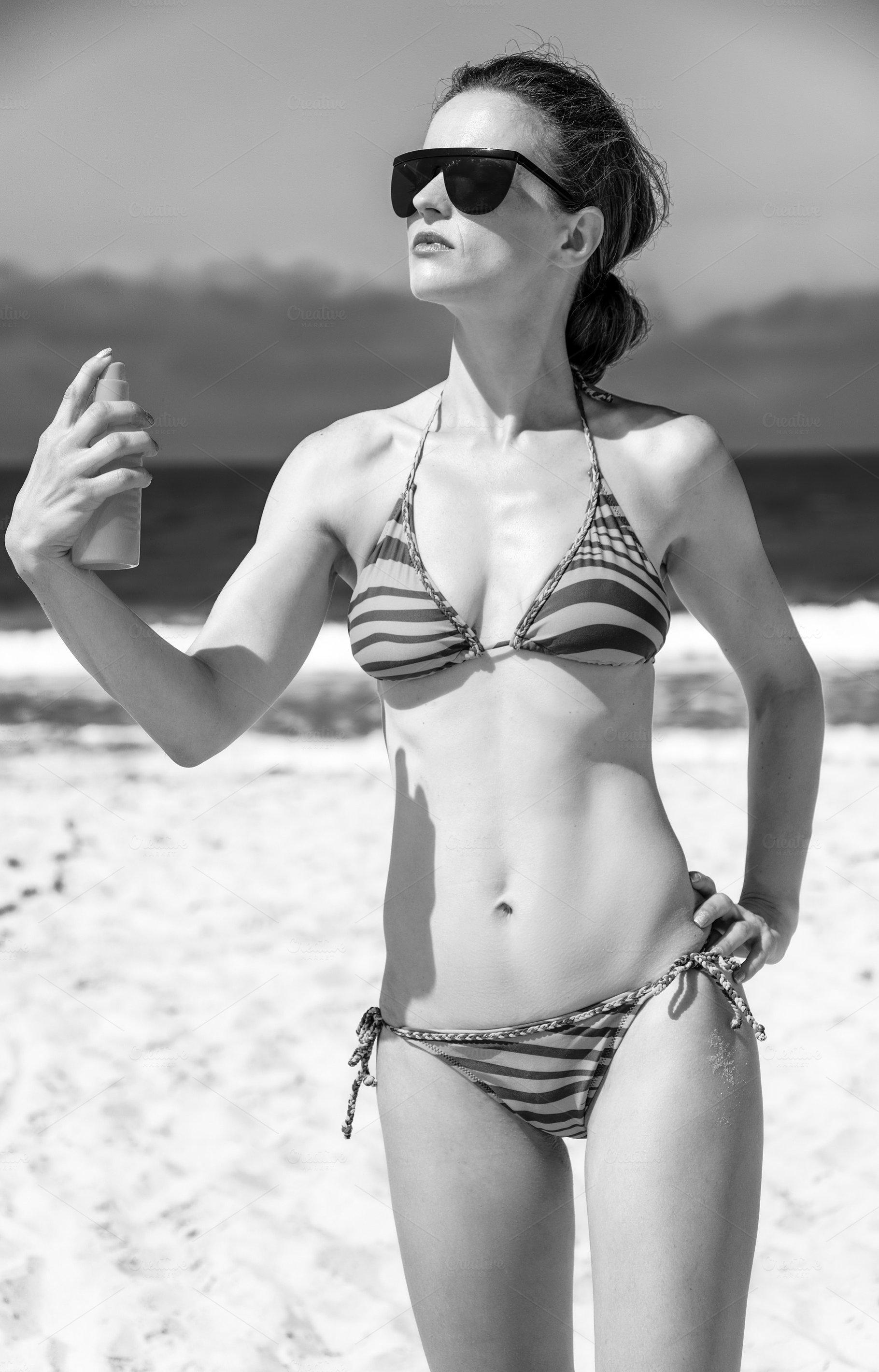 1dc0b77bc914e young woman on beach applying suntan lotion ~ People Photos ...