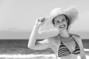 happy modern woman in bikini and beach straw hat on the seashore