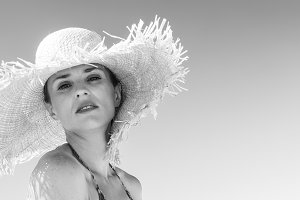 young woman in bikini and beach straw hat on seacoast