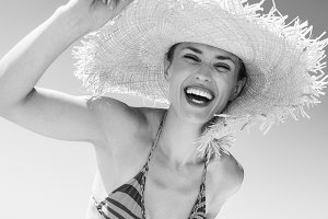 happy young woman in swimwear and beach straw hat on seashore