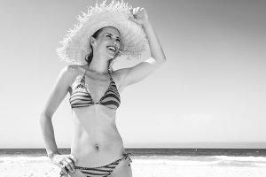 woman in beach straw hat on seacoast looking into distance