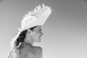 smiling woman in beach straw hat on seacoast looking aside