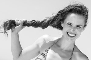 happy modern woman on seacoast holding long brunette hair