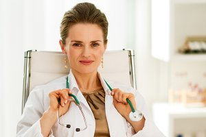 happy medical doctor woman sitting in office
