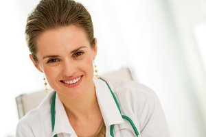 smiling medical doctor woman sitting in office