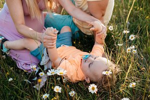 Child resting in grass with parents.