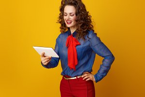 happy stylish woman against yellow background using tablet PC