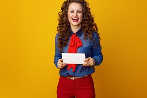 happy trendy woman against yellow background with tablet PC