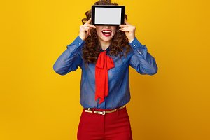 happy stylish woman hiding behind tablet PC blank screen