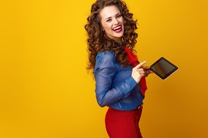 smiling young woman on yellow background using tablet PC