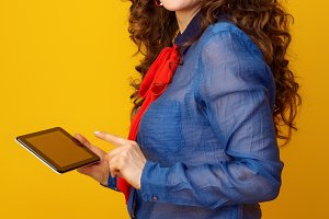 happy modern woman against yellow background using tablet PC