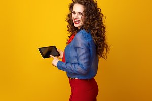happy young woman on yellow background using tablet PC