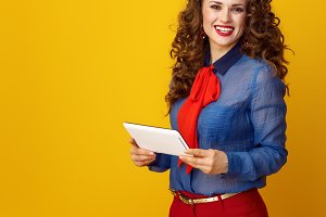 smiling trendy woman on yellow background with tablet PC