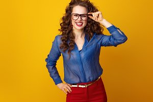 smiling trendy woman in glasses isolated on yellow background