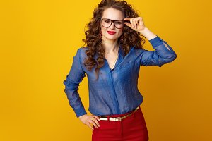 happy modern woman in glasses against yellow background