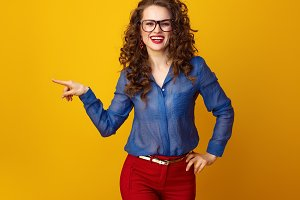 smiling stylish woman in glasses pointing at something