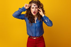 stylish woman in glasses on yellow background squinting